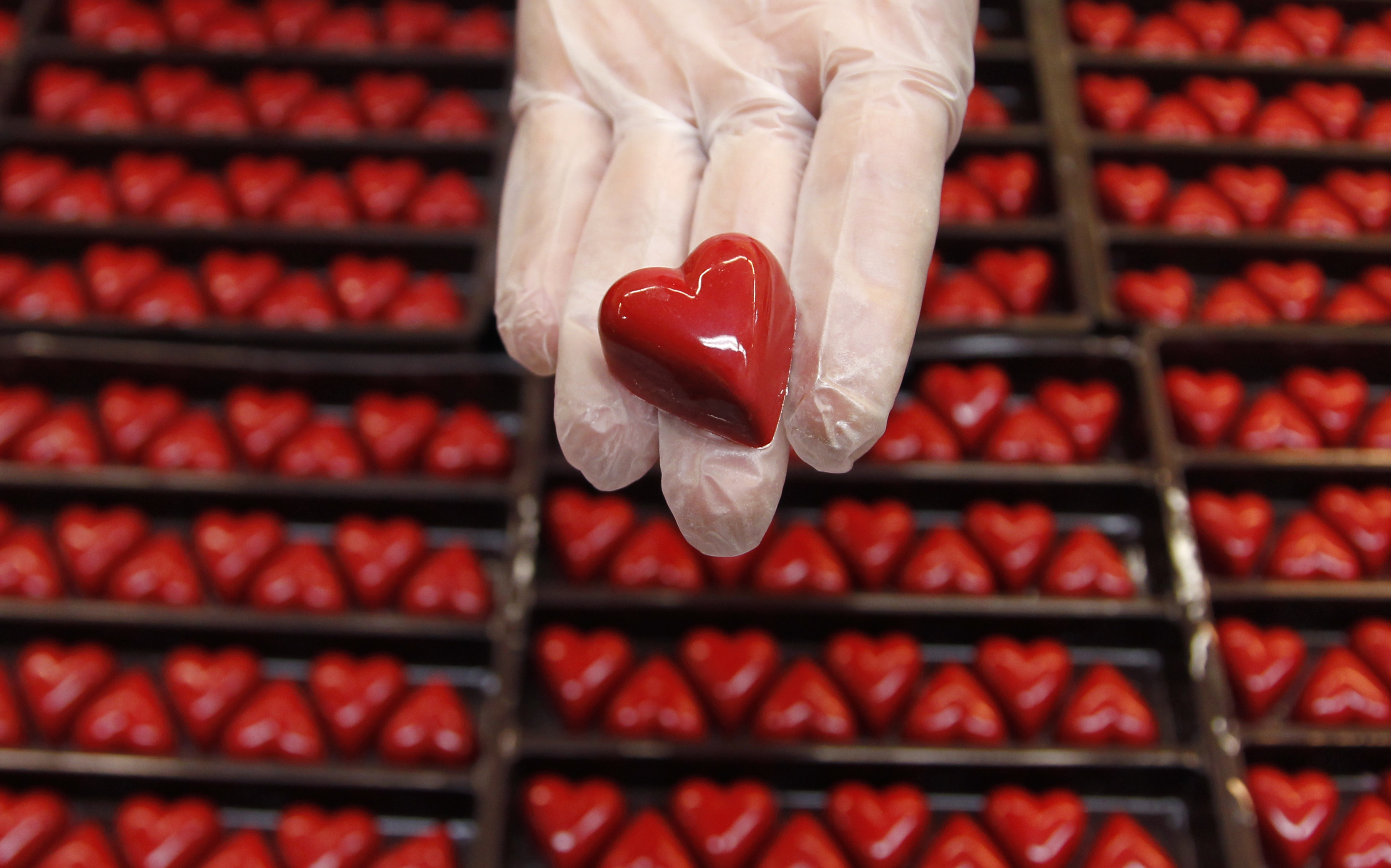 A worker displays a heart-shaped praline for Valentine's Day at a Wittamer chocolate boutique in Brussels
